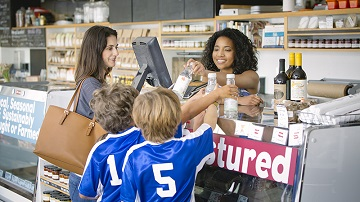Woman with two boys making purchases from clerk at grocery store counter.